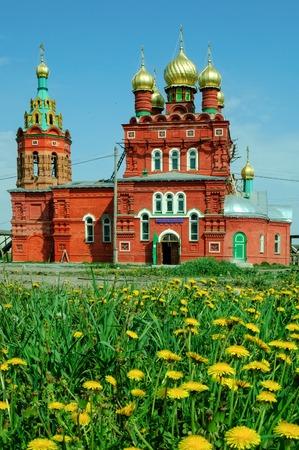 nikolay: Temple for sake of Saint Nikolay Chudotvorts behind dandelion flowers. Kulakovo. Tyumen region. Russia Stock Photo
