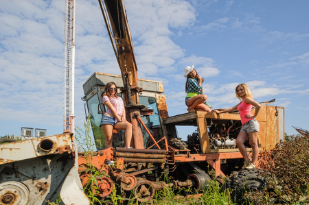 Three sexy attractive women stand on old agriculture harvester in farm photo