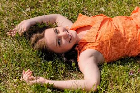Beautiful Young Woman Outdoors. Enjoy Nature. Healthy Smiling Girl in Green Grass. photo