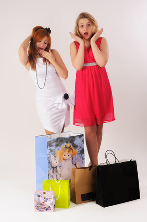 Young attractive women with shopping bags screaming and wondering over white background photo