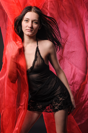 Shot of a sexy woman in lingerie over red textile background photo