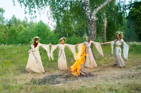 springbreak: Four attractive Women with Wreath of Flowers dancing around bonfire. Ivan Kupala Holiday Celebration. Russia