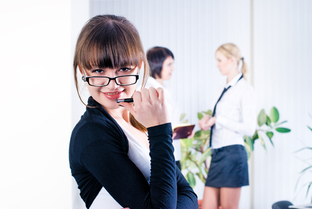 Pretty business woman in office at collegues background photo
