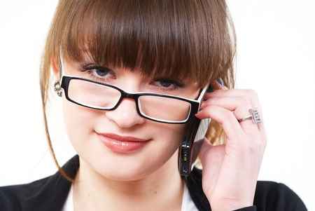 Young smiling woman talking by mobile phone at isolated backgtound photo