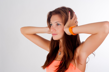 Attractive young woman covering her ears - Hear no evil gesture over white background