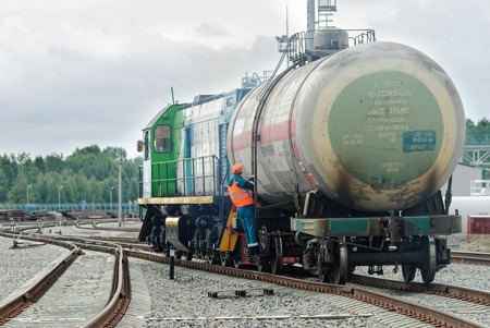 iron man: Tobolsk, Russia - July 15. 2016: Sibur company. Denisovka railway station. Shunting locomotive transports the tank on other way