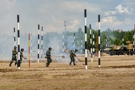 infantry: Tyumen, Russia - June 21, 2017: Army Games. Safe Route contest. 4 engineers with mine detectors move and make a pass Editorial
