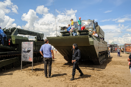 tracked: Tyumen, Russia - June 21, 2017: Army Games. Audience is photographed on tracked amphibious carrier PTS-4 with truck on board