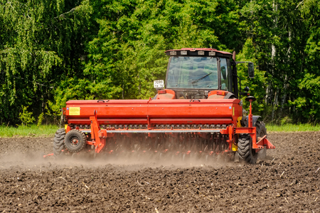 Verhovina, Russia - June 14, 2016: Farmer with tractor seeding - sowing crops at agricultural fields