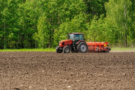 agrarian: Verhovina, Russia - June 14, 2016: Farmer with tractor seeding - sowing crops at agricultural fields
