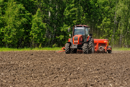 Verhovina, Russia - June 14, 2016: Agriculture tractor sowing seeds and cultivating field Stok Fotoğraf - 81255128