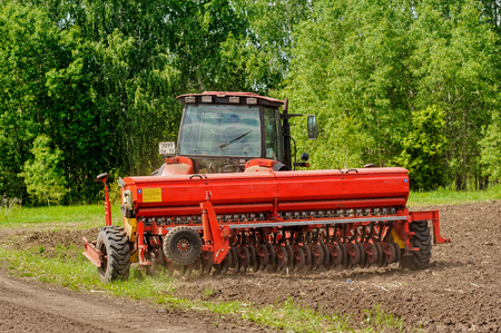 Verhovina, Russia - June 14, 2016: Agriculture tractor sowing seeds and cultivating field Editöryel