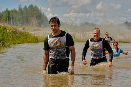 carrera de relevos: Tyumen, Russia - July 1, 2017: Race of Heroes project on the ground of the highest military and engineering school. Water stage. Teams running