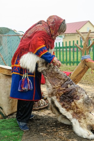 Tyumen, Russia - June 24, 2016: The 5th open championship of Russia on a plowed land. Nenets woman processes cervine skin in cultural center of North people. Nenets - aboriginals of Russian North Editorial