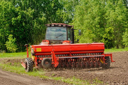 Agriculture tractor sowing seeds and cultivating field