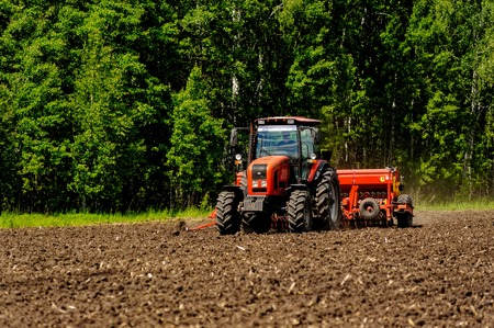Verhovina, Russia - June 30, 2017: Farmer with tractor seeding - sowing crops at agricultural fields
