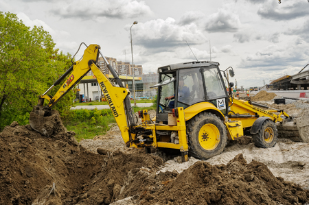 Tyumen, Russia - June 1, 2017: JSC Mostostroy-11. Construction of two-level outcome on bypass road on Fedyuninskogo and Permyakova streets intersection. Working Excavator Tractor Digging A Trench