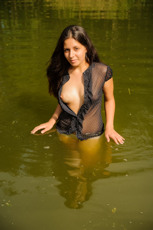 Sexy young nude woman in transparent blouse relaxing in water