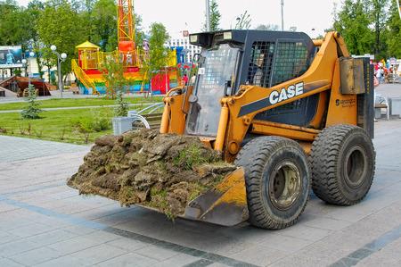 Tyumen, Russia - June 17. 2006: Tsvetnoy Bulvar city park. Skid loader working on gardening Editorial