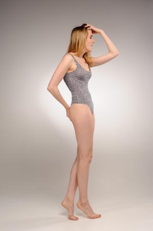 Portret van aantrekkelijke jonge vrouw met verrast emoties over grijze achtergrond