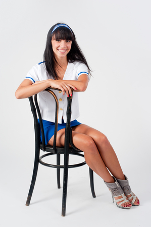 Attractive young smiling stewardess sitting on vintage chair over white background Stock Photo