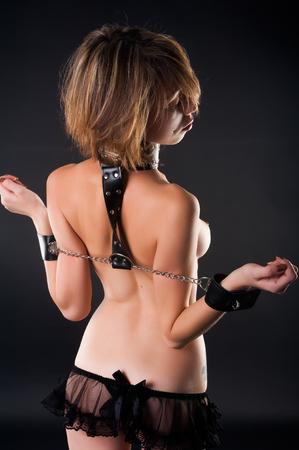 Woman with handcuffs. Bondage concept. Studio shot