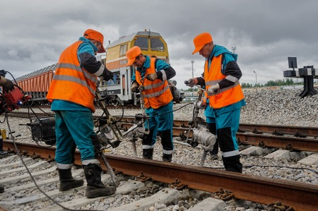Tobolsk, Russia - July 15. 2016: Sibur company. Denisovka railway station. Railway workers repairing rail in rainy weather 新聞圖片
