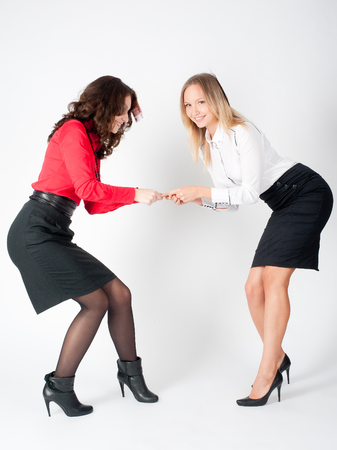 Two young funny business ladies argue because of paper money over white background