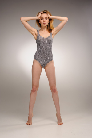 Fit young woman standing in gymnastic suit and holds her head over grey background