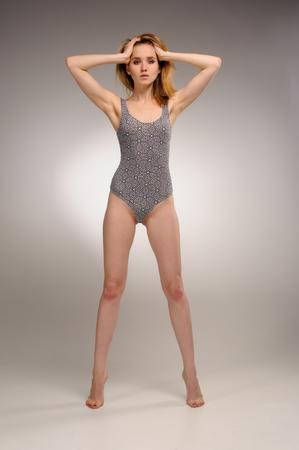 Fit jeune femme debout dans un costume de gymnastique et tient sa tête sur fond gris Banque d'images - 92037865