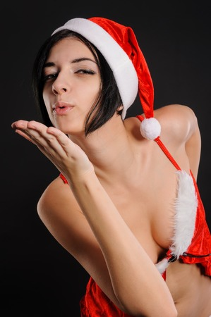 Beautiful caucasian young happy woman with healthy skin and charming smile wearing red dress and Christmas hat sending air kiss on black background