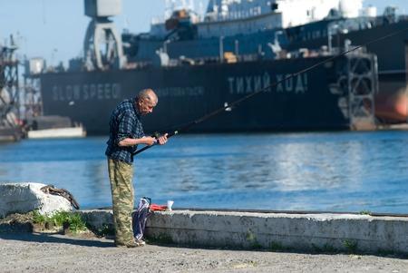 Baltiysk, Russia - June 29, 2010: Senior fisherman gets bait on ship in dry dock background. Harbor