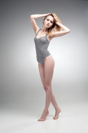 Portret van aantrekkelijke jonge vrouw met verraste emotie over grijze achtergrond Stockfoto