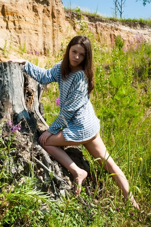 Portrait of young attractive brunette woman standing on stump
