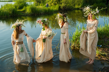 Four attractive women with wreath of flowers enter in lake water. Ivan Kupala Holiday Celebration
