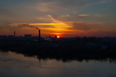 Tyumen, Russia - May 1, 2005: Silhouettes of plywood factory on river bank and Holy Trinity Monastery Stock Photo