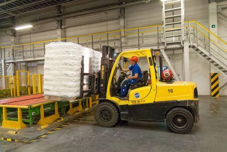 Tobolsk, Russland - 15. Juli 2016: Firma Sibur. Polymeranlage. Fahrer auf Gabelstapler belädt Paletten mit Fertigwaren von der Verpackungsmaschine zum Lager