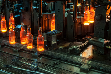 Automated line for the production of glass containers. The hot bottles are put on a moving conveyor Banco de Imagens