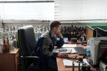 Bogandinskiy, Russia - April 20, 2018: Stekloteh factory on bottles production. Engineer works on PC