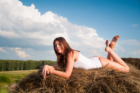 Sexy young brunette woman relaxing on hay stack