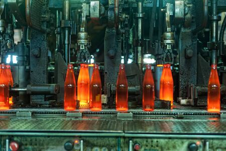 Bogandinskiy, Russia - April 20, 2018: Stekloteh factory on bottles production. Automated line for the production of glass containers. The hot bottles are put on a moving conveyor Stock Photo - 128834505