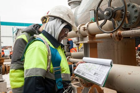 Tobolsk, Russia - May 29. 2018: Sibur company. Construction of plant on processing of hydrocarbons. Construction worker on a construction site checks documents