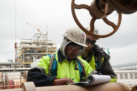 Tobolsk, Russia - May 29. 2018: Sibur company. Construction of plant on processing of hydrocarbons. Construction worker on a construction site check documents Editorial
