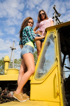 Two sexy attractive woman standing on old big tractor