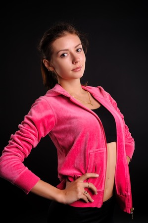 Young sexy sporty woman over black background Stock fotó