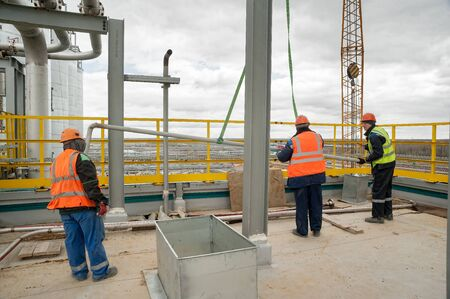 Tobolsk, Russia - May 29. 2018: Sibur company. Construction of plant on processing of hydrocarbonic raw materials. Construction workers standing on roof and placing pipe lifted by crane