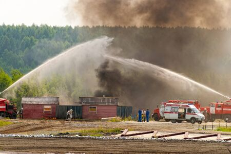 Nizhniy Tagil, Russia - July 12, 2008: Special firefighting vehicle SPM. Display of opportunities of equipment. Russia Arms Expo-2008 exhibition. Firefighter and ambulance team work at fire