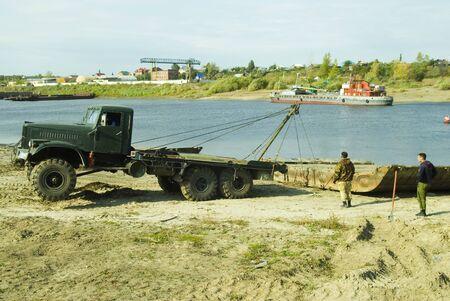 Tyumen, Russia - September 19, 2009: Truck is pulling module of pontoon bridge from Tura river