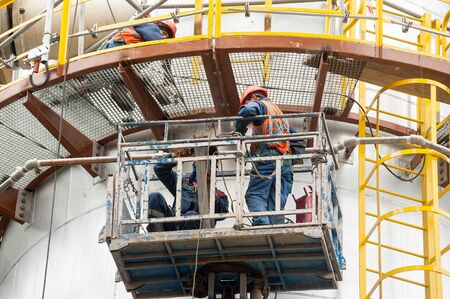 Tobolsk, Russia - May 29. 2018: Sibur company. Construction of plant on processing of hydrocarbons. Two construction workers in lifting cage on height