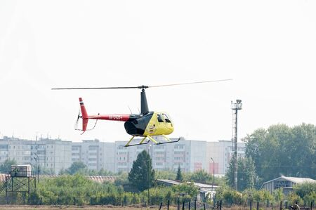 Tyumen, Russia - August 11, 2012: On a visit at UTair airshow in heliport Plehanovo. Pilot of Aerospatiale AS-350B3e Ecureuil shows flying opportunities